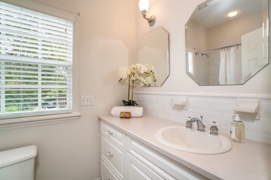 Bathroom with drawn blinds and countertop with rolled towel and orchid on it.