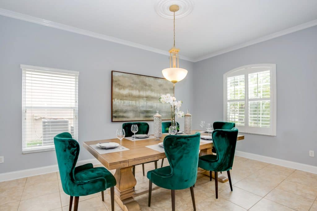 A dining room area with a table and emerald green Parson chairs.