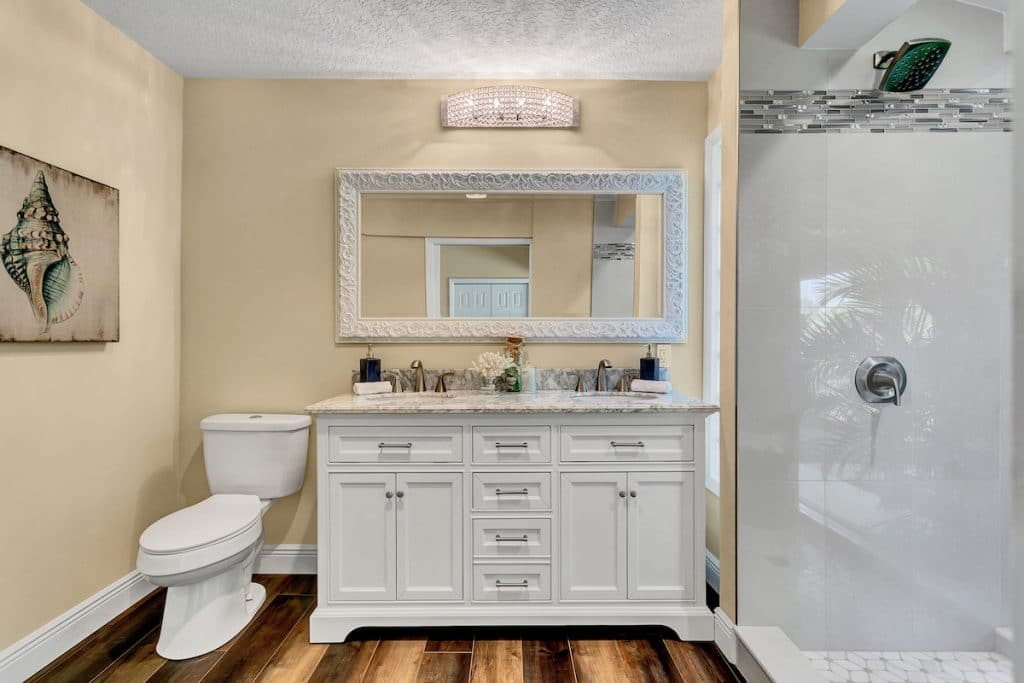 Bathroom with shell artwork, toilet, double sink cabinetry, mirror, and stand-up shower.