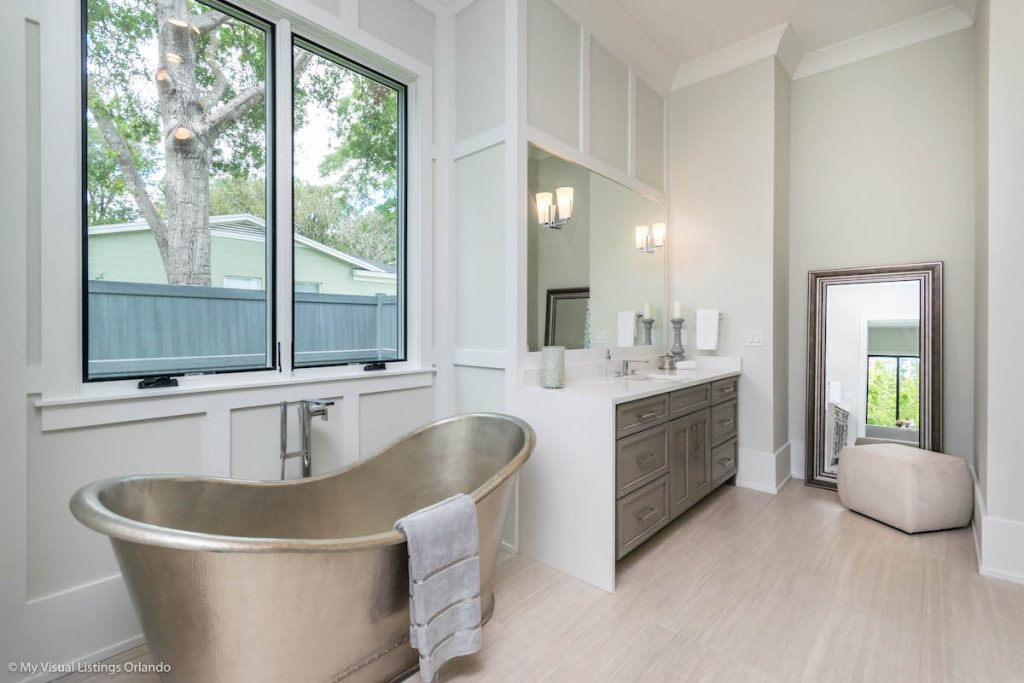 A large bathroom with silver freestanding tub, vanity area, full-length mirror, and seating.