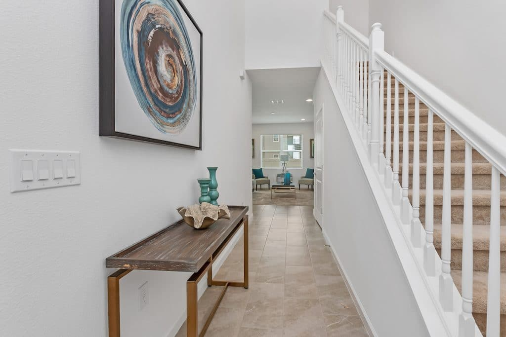 Entryway with view of stairway, console table, decorative items with artwork above.