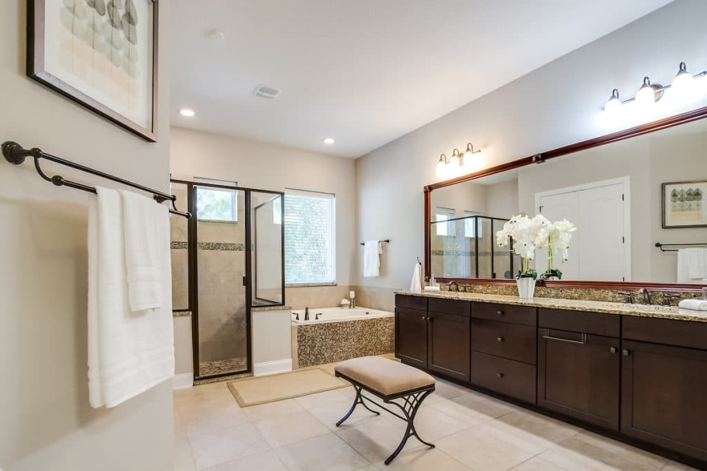 Large bathroom with large countertop area, stand-up shower, and tub staged by MHM Professional Staging.