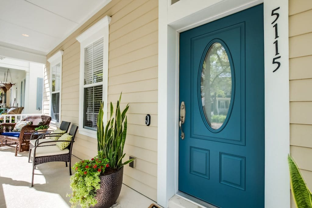 Close up of a teal front door and front porch with potted plants.