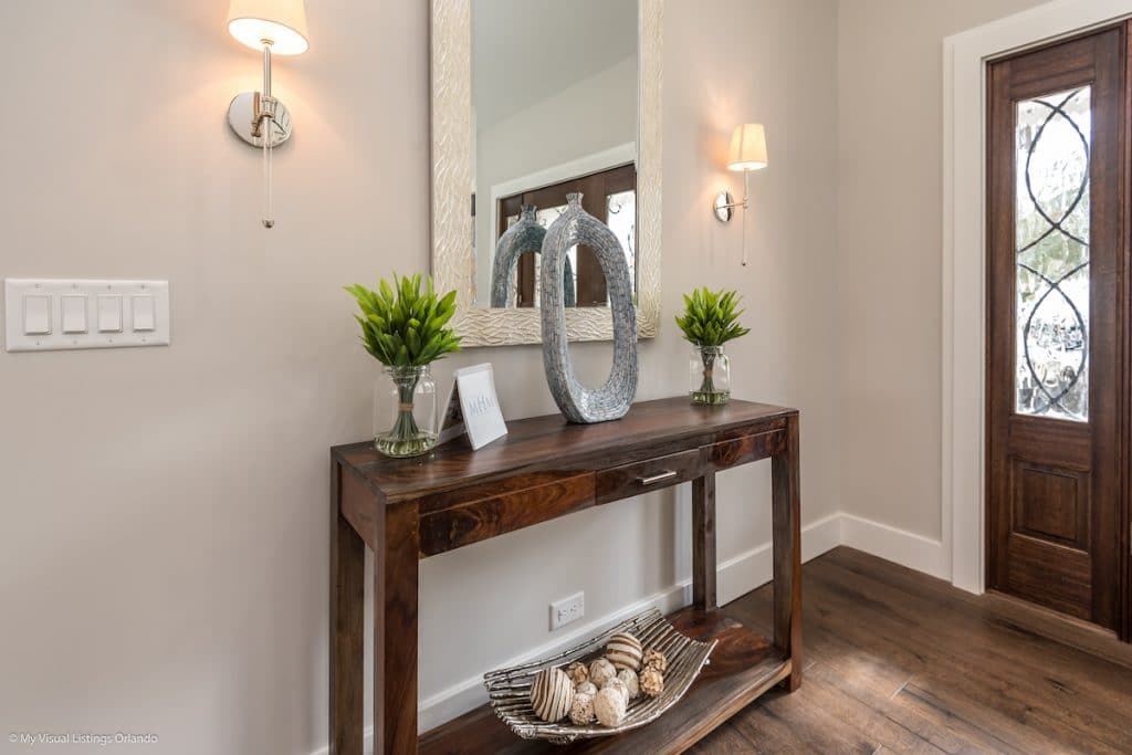 Entryway with mounted lights, console table, and decorative mirror above.