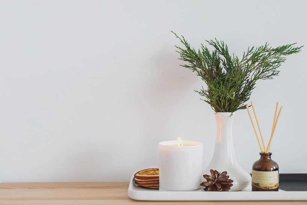 A tray filled with a candle, greenery, and pinecone.