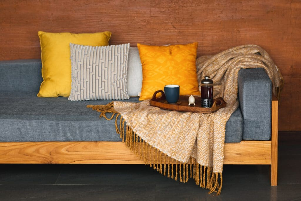 Outdoor porch bench with throw pillows, a blanket, and a tray of coffee.