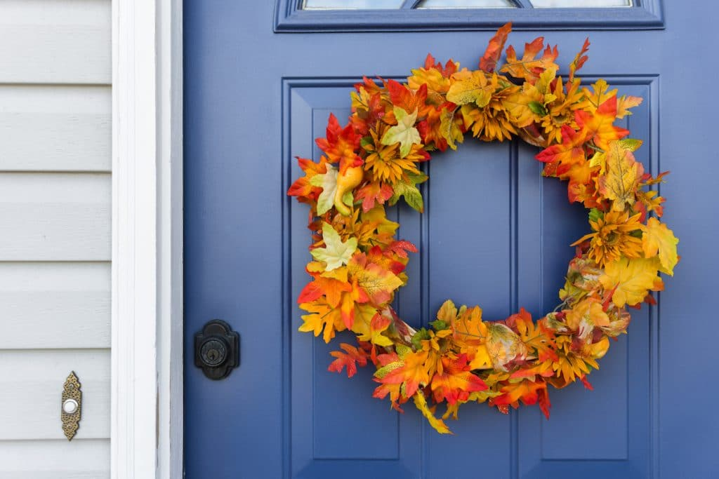 Close up of a blue front door with a colorful autumn wreath.
