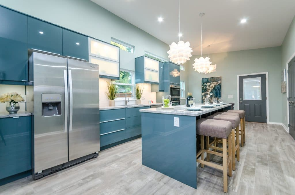 A beautiful kitchen with glossy teal cabinetry and a kitchen island with oversized bar stools.