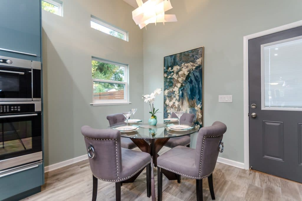 An eat in kitchen with lavender dining chairs and a vertical art piece that accentuates the high ceiling.