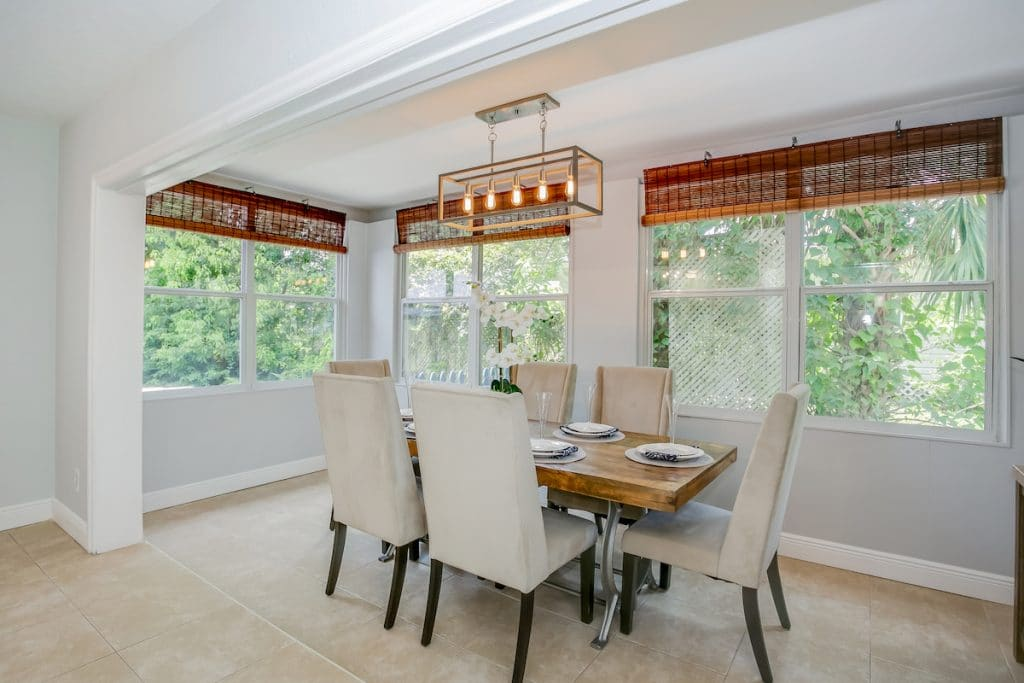Dining area with dining table, parson chairs, geometric light, and natural textured blinds.