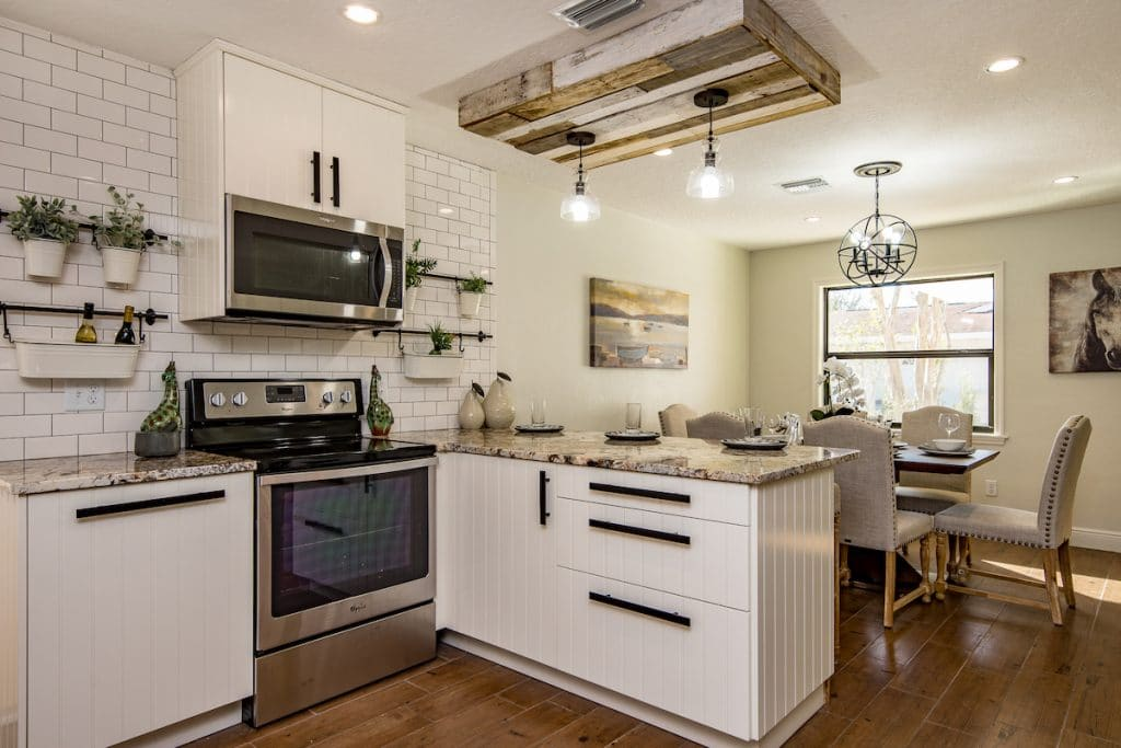 Gorgeous farmhouse kitchen with white subway tile, granite countertops, and a small hanging garden.