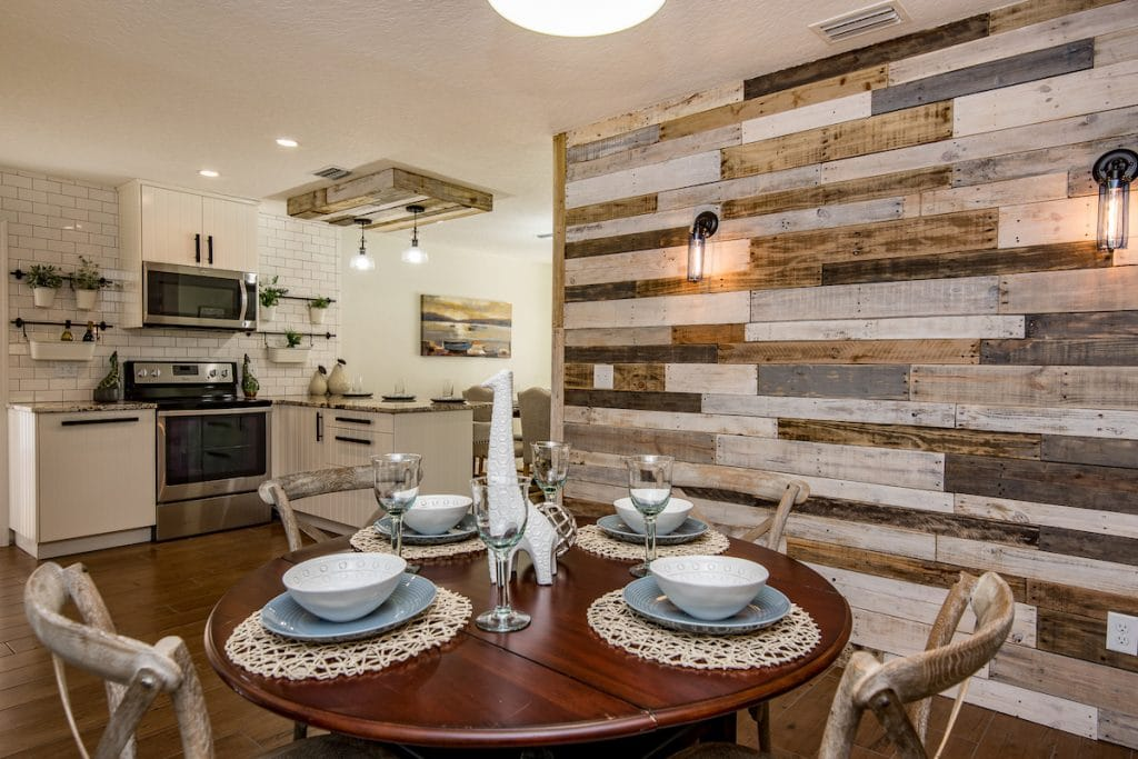 A breakfast nook with unique accent wall made of wood palettes and round dining set.