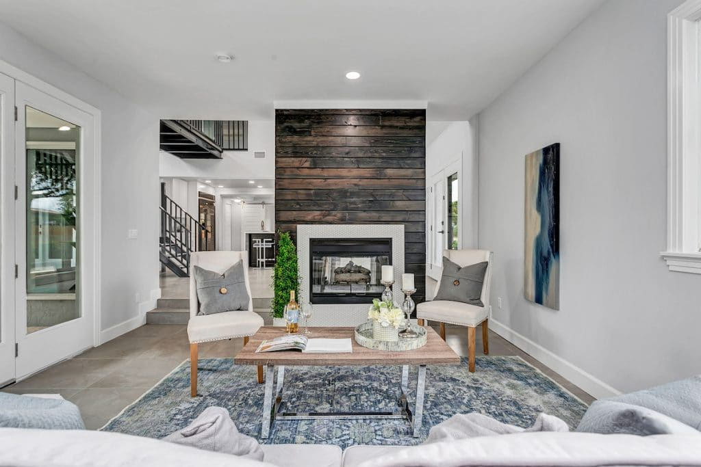 Staged living area with view of beautiful fireplace inset a wood planked wall.