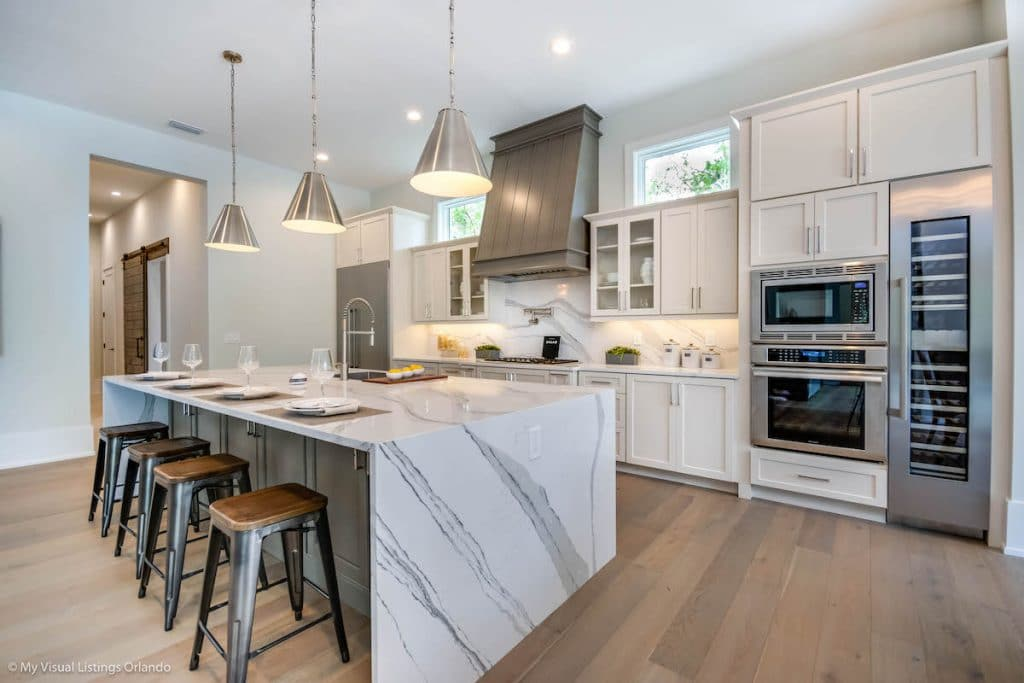 Kitchen with marble kitchen island and silver pendant lights above it.