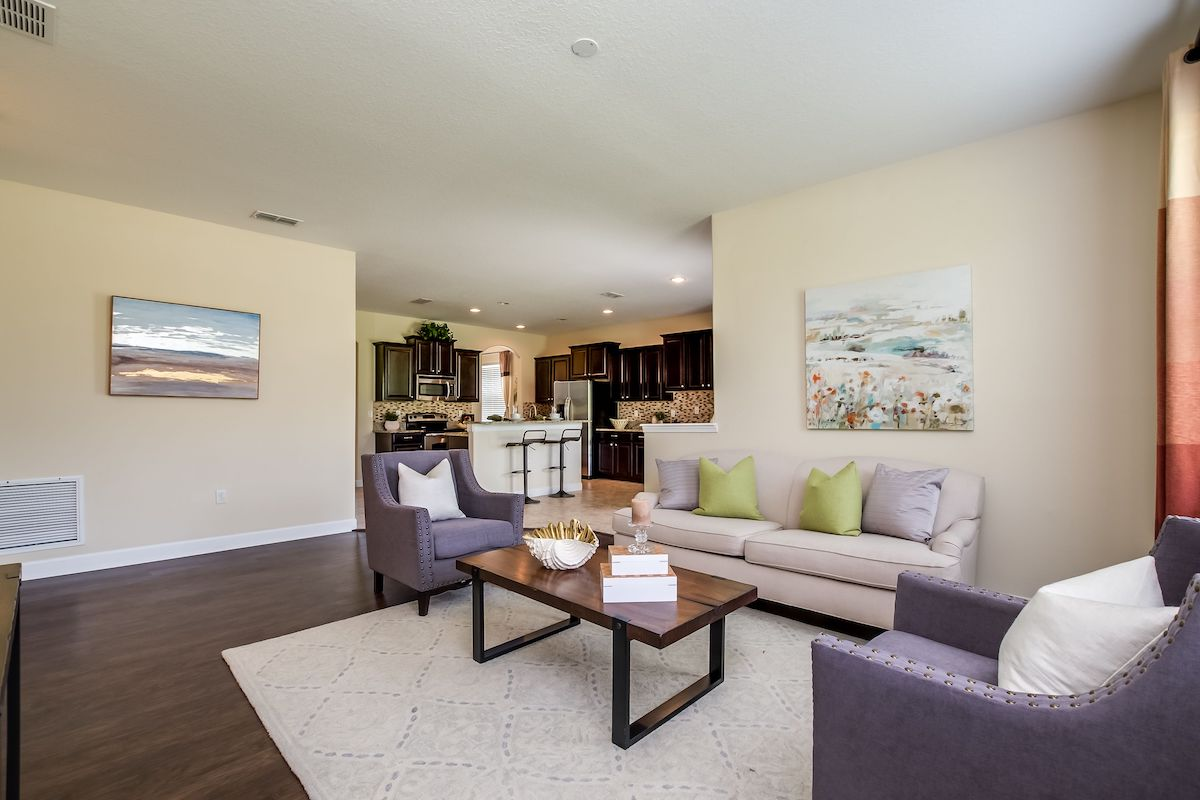 Living room with neutral sofa, throw pillows, purple armchairs, rug, and coffee table.