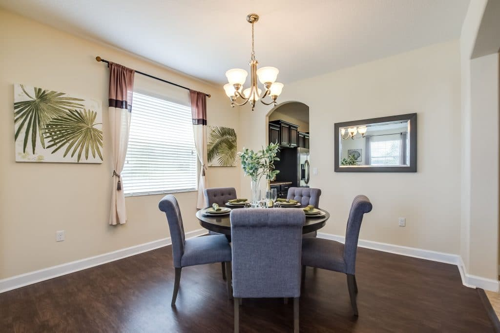 Dining room with round dining table, Parson chairs, palm artwork, and dark wood floors.