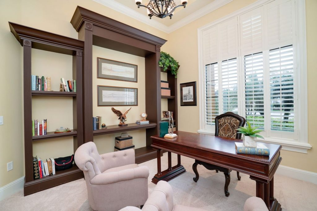 Home office with dark wood desk and shelving.