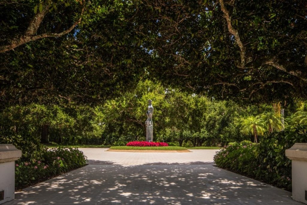 Private driveway with statue in the center and lush greenery surrounding it.