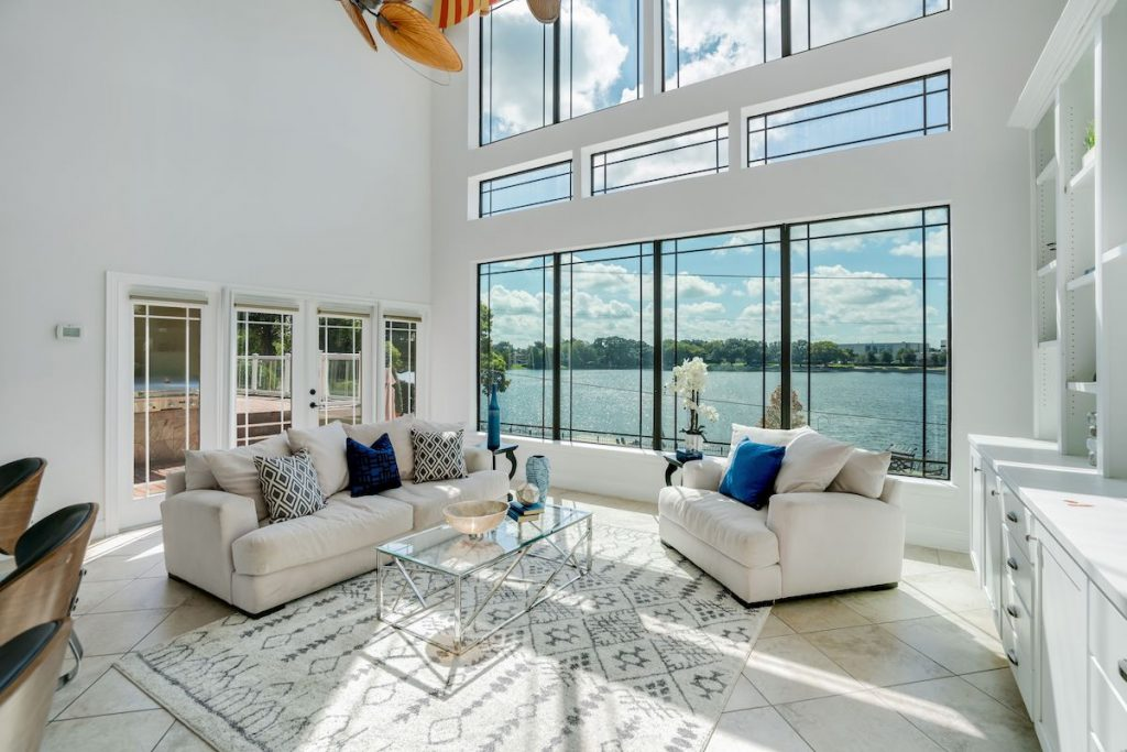 A living room with high ceilings and large windows with view of lake.