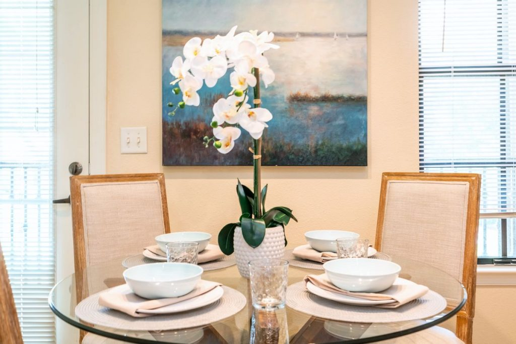 A small round dining table with place settings and a white faux orchid in the middle.
