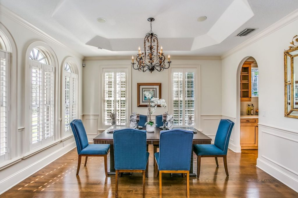A dining room with shiny wood floors staged by MHM Professional Staging.