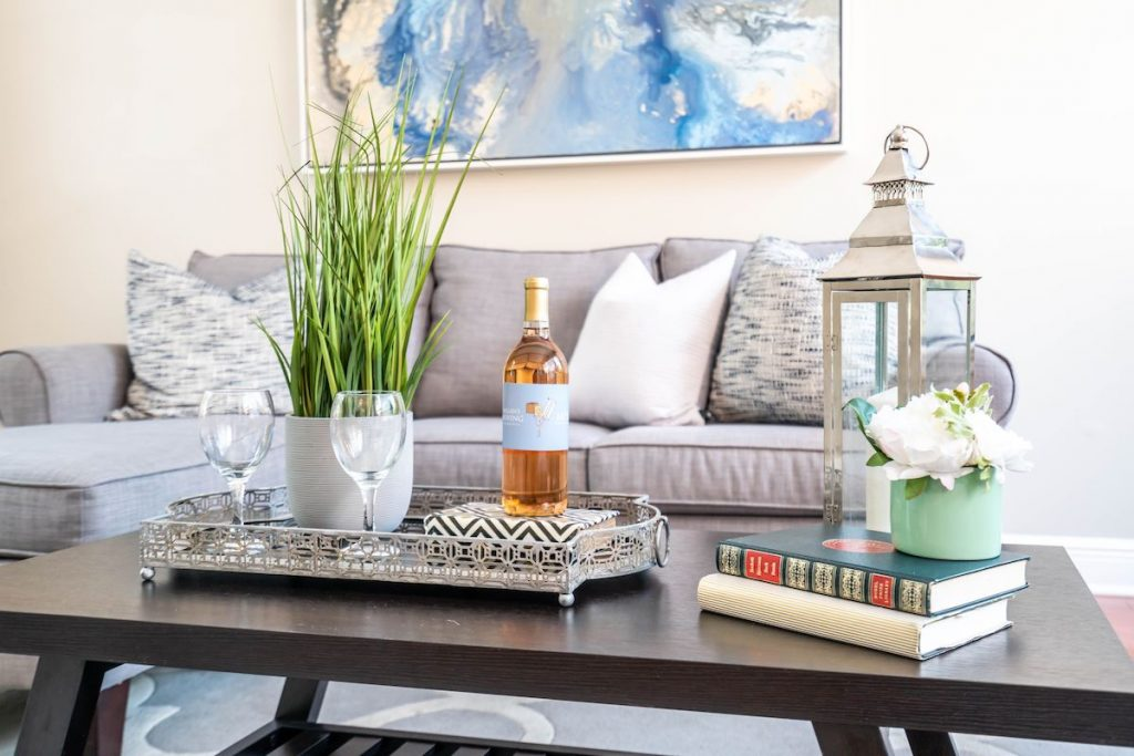 Coffee table with stacked books and vase of faux flowers on top.
