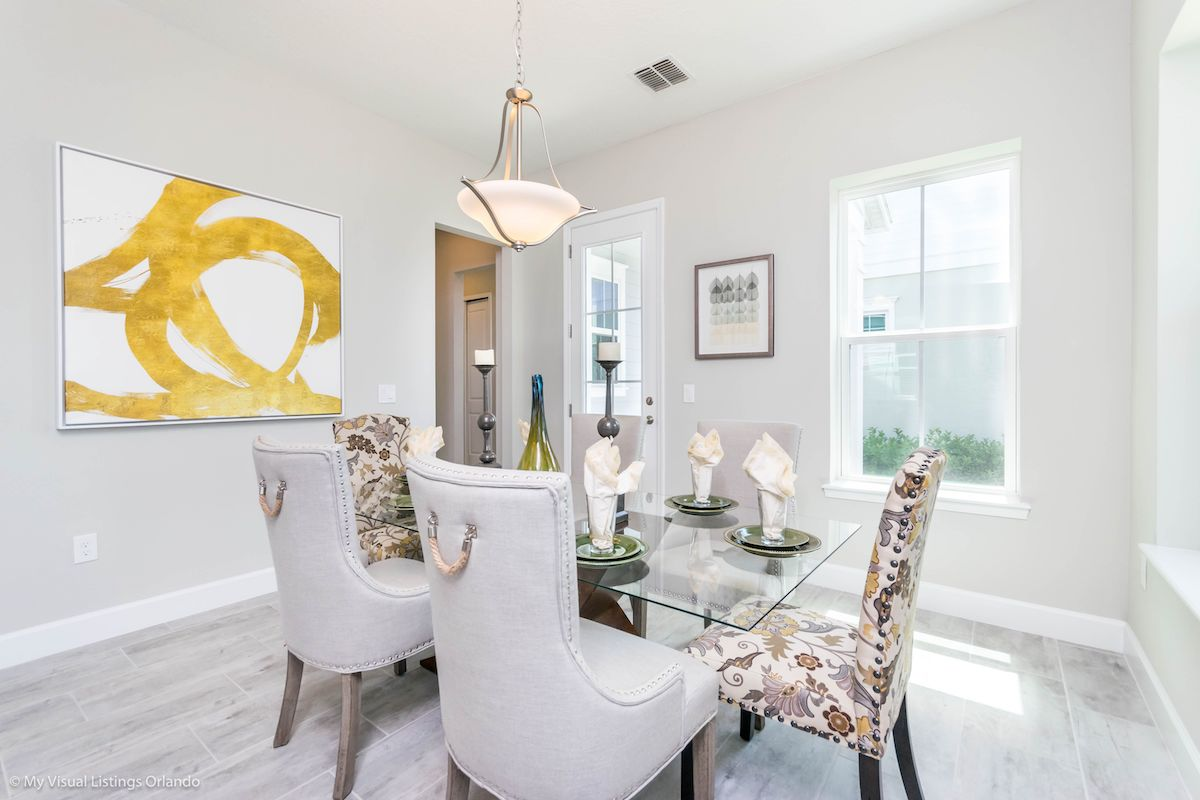 A dining room with gold abstract painting on the wall.
