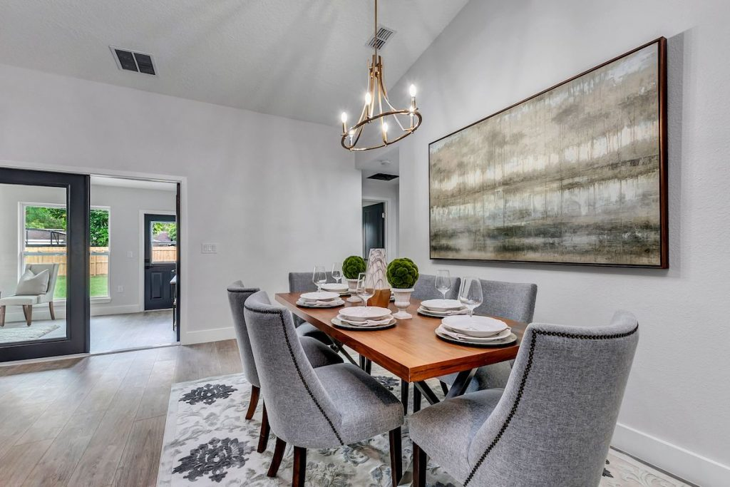 A dining room with a large horizontal painting above the dining table with neutral imagery.