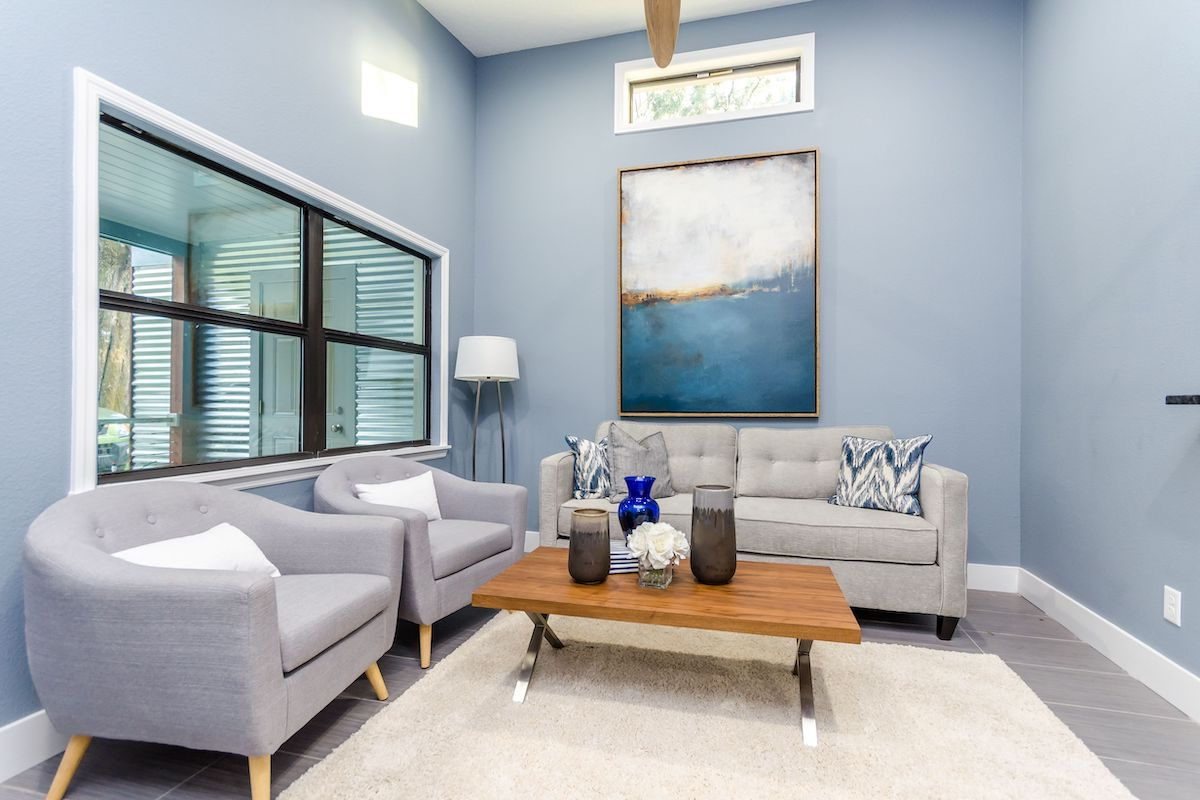 A living area with blue walls, a window, and artwork on the wall.