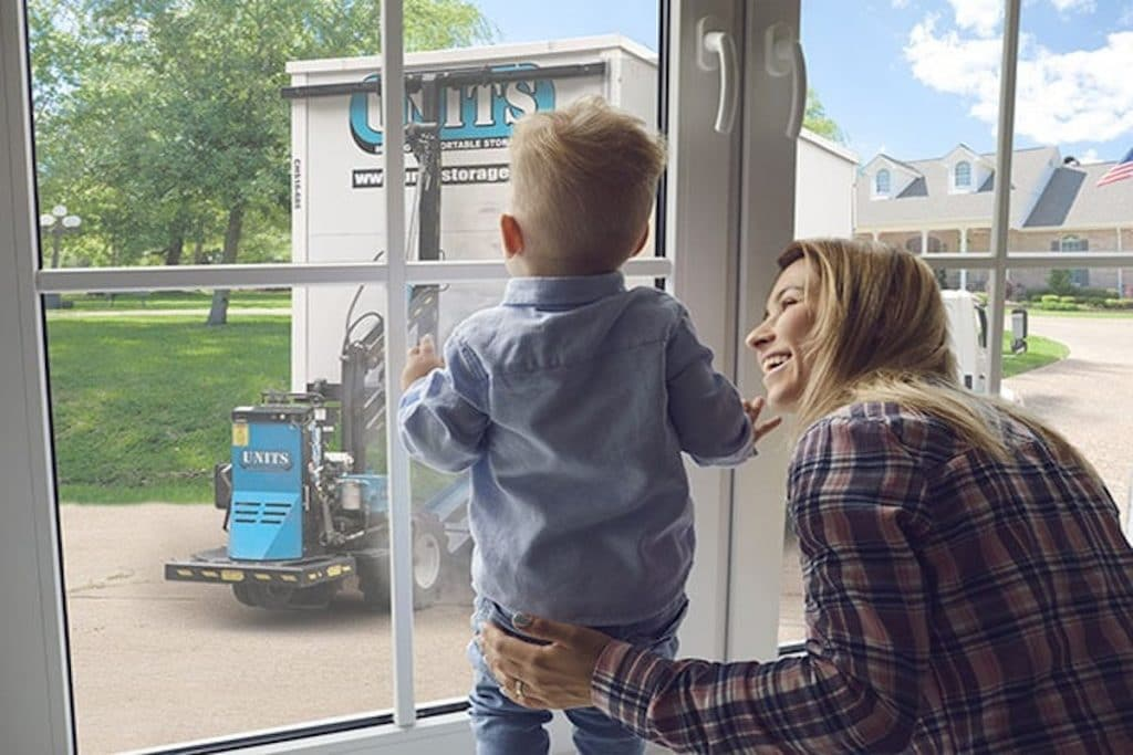 A Caucasian woman smiling at her son with a view of a UNITS container outside the window.