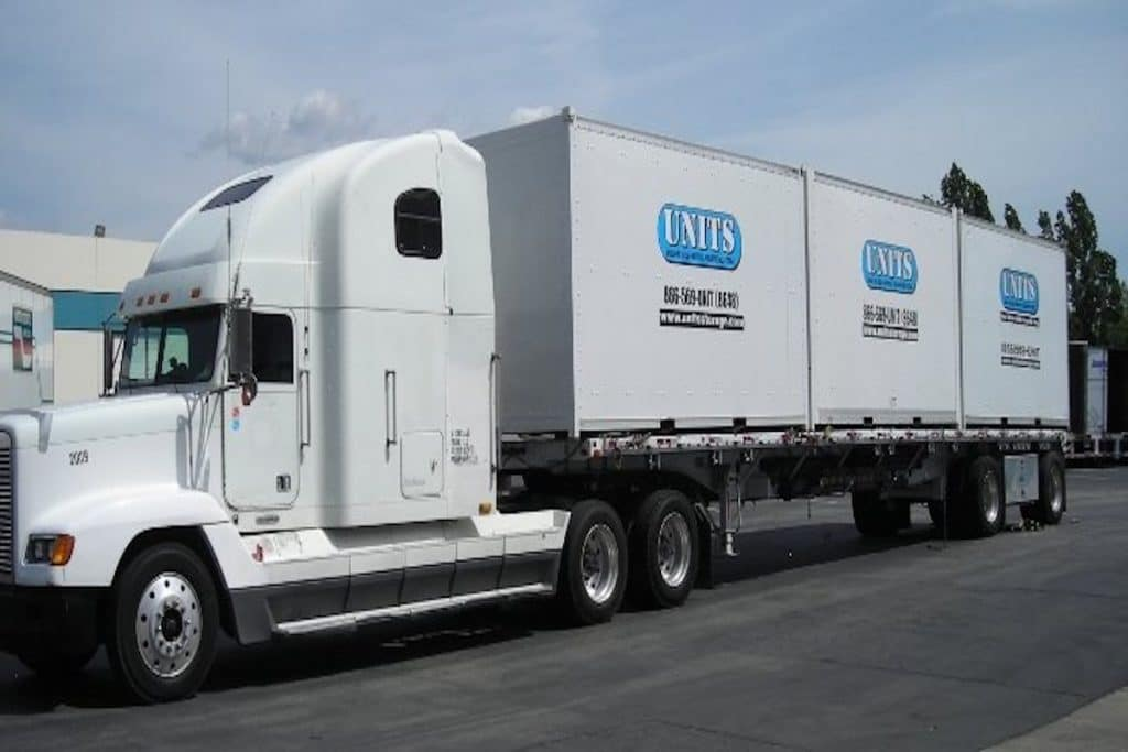 A truck with three UNITS storage containers loaded.