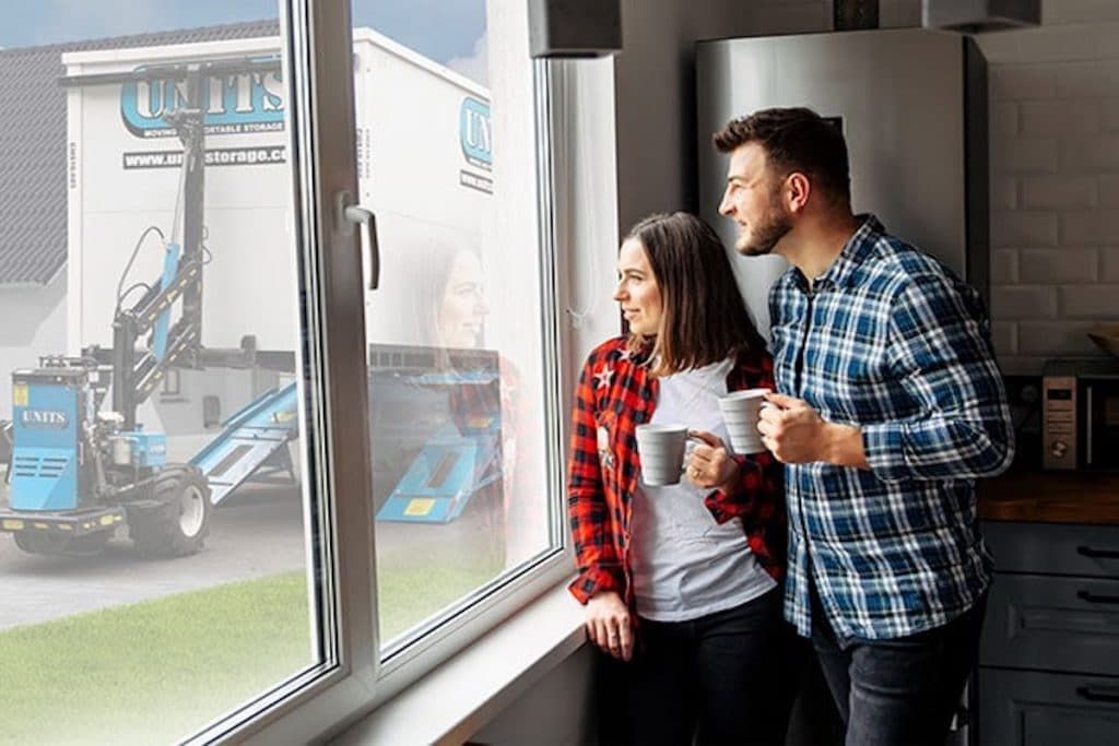 A young couple holding mugs looking outside the window with view of UNITS container.