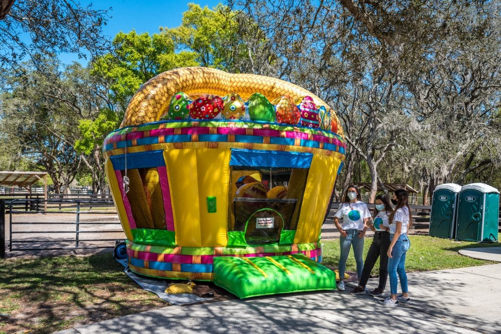 Bouncehouse with three girls standing outside.