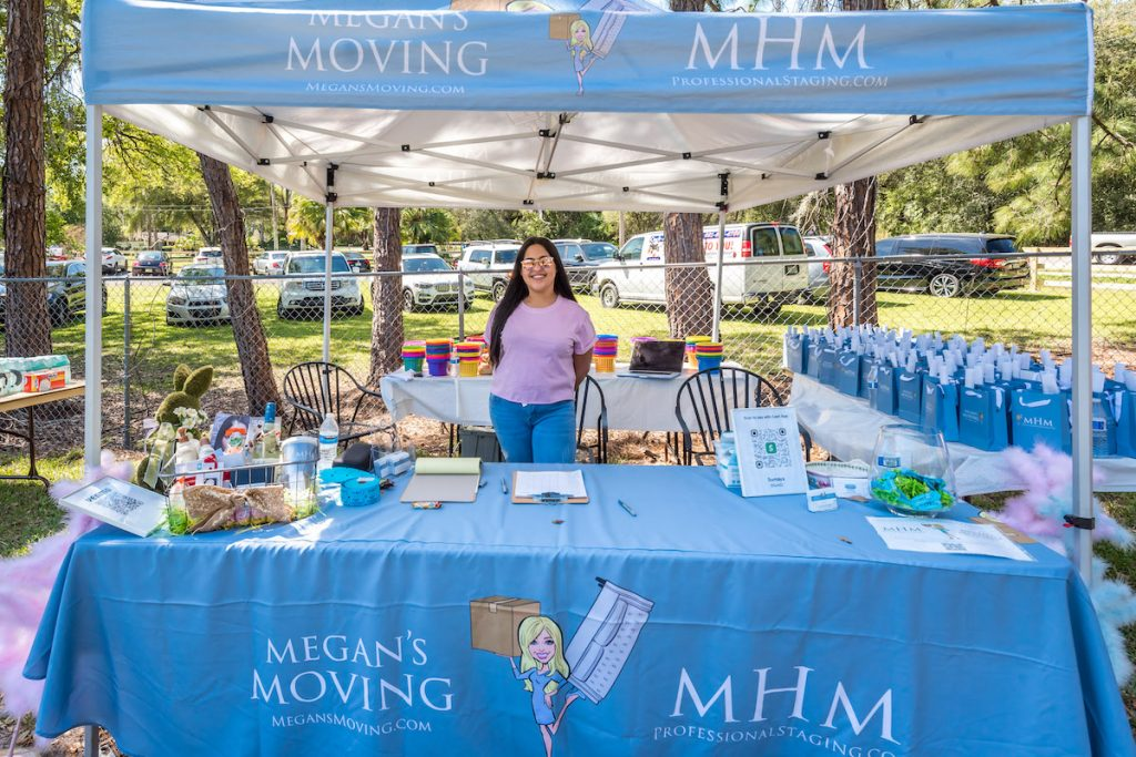 The Megan's Moving and MHM Professional staging tent with team member.