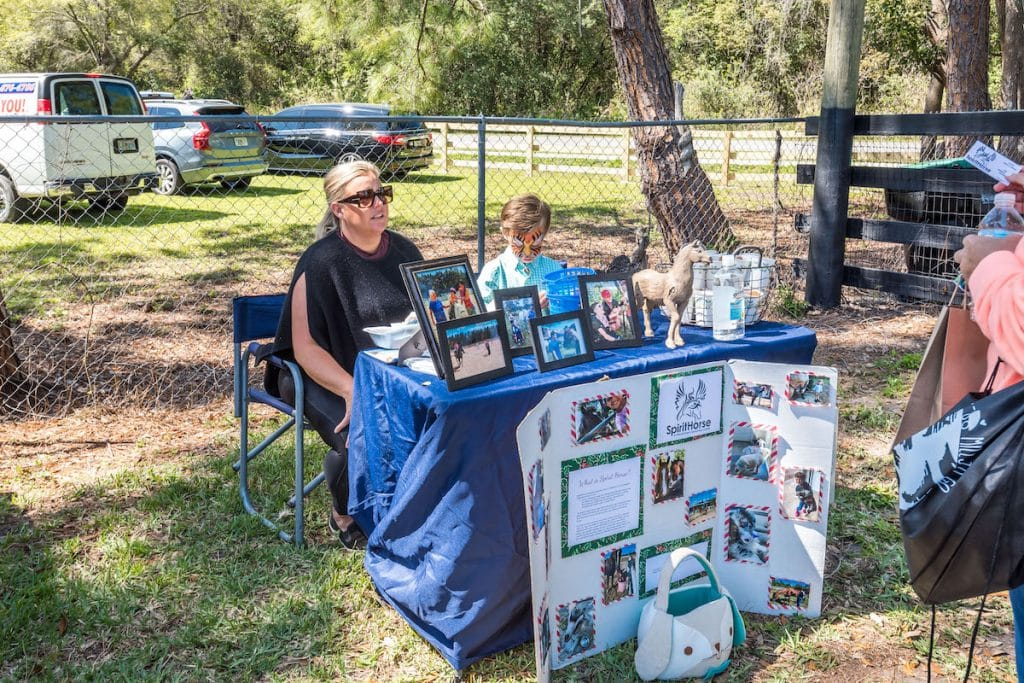 A woman and a child behind the Spirit Horse table and display.