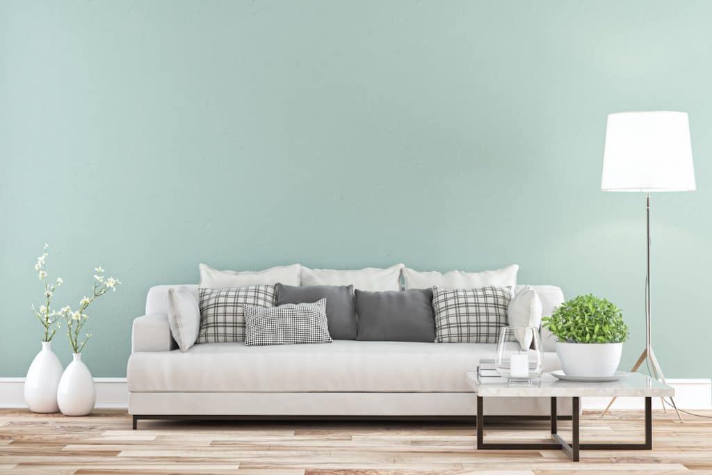 A living room with neutral couch, floor lamp, and a mint green wall.