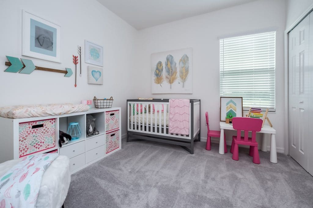 A room staged as a children's nursery with crib, changing table, and kids table.