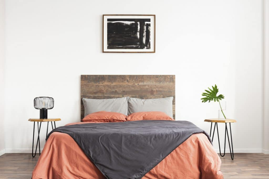 A bedroom with wooden headboard , end tables, and coral and gray sheets.