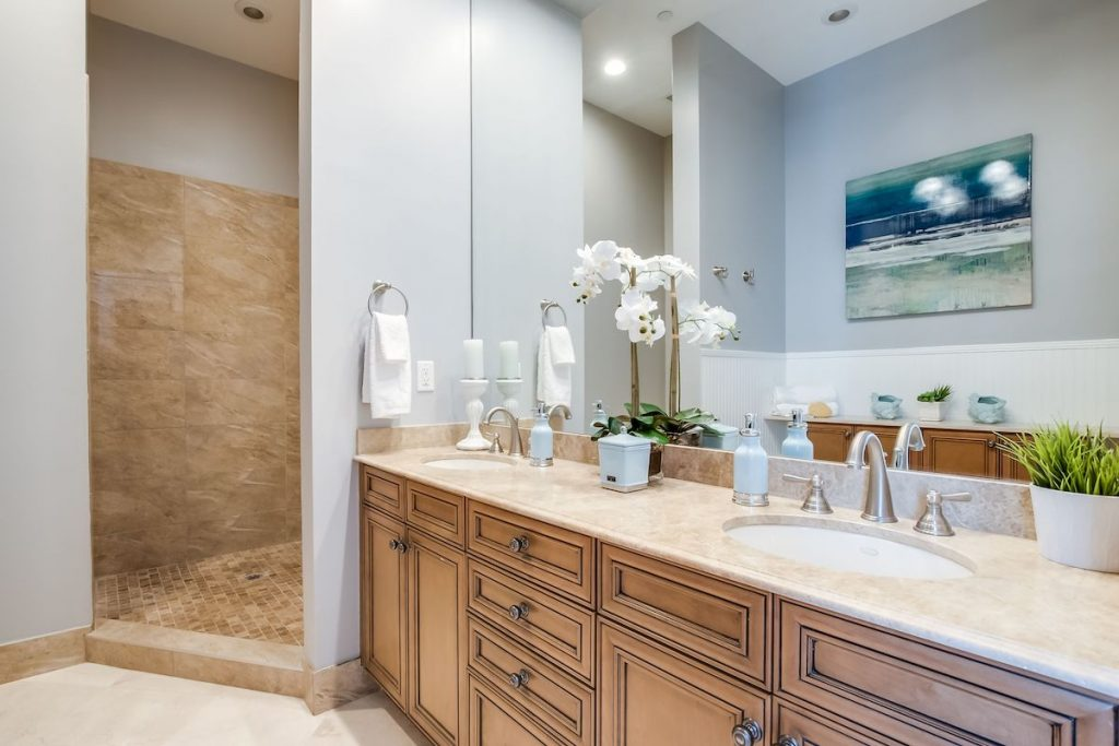 A bathroom with light blue walls and silver fixtures.