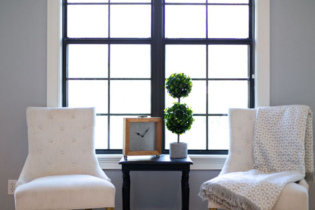 Two accent chairs and table near a window and accent wall.
