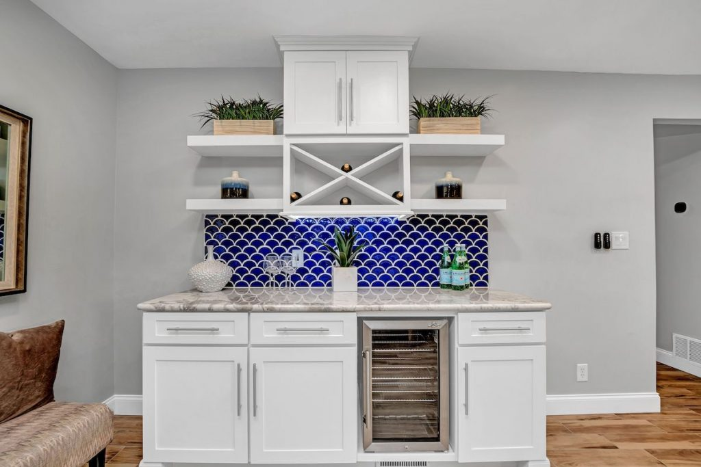 A bar area with white cabinetry against light blue walls.
