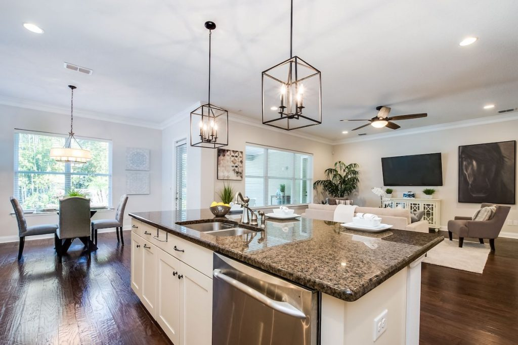 An open floor plan with kitchen, dining room, and living room in sight with dark metallic pendant lights.