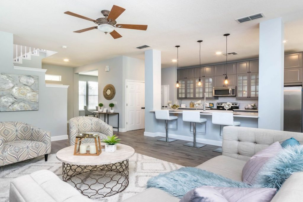 An open floor plan with view of kitchen and living room with ceiling fan.