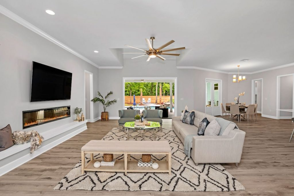A large open floor plan with view of living room, tv, ceiling fan, and dining room.