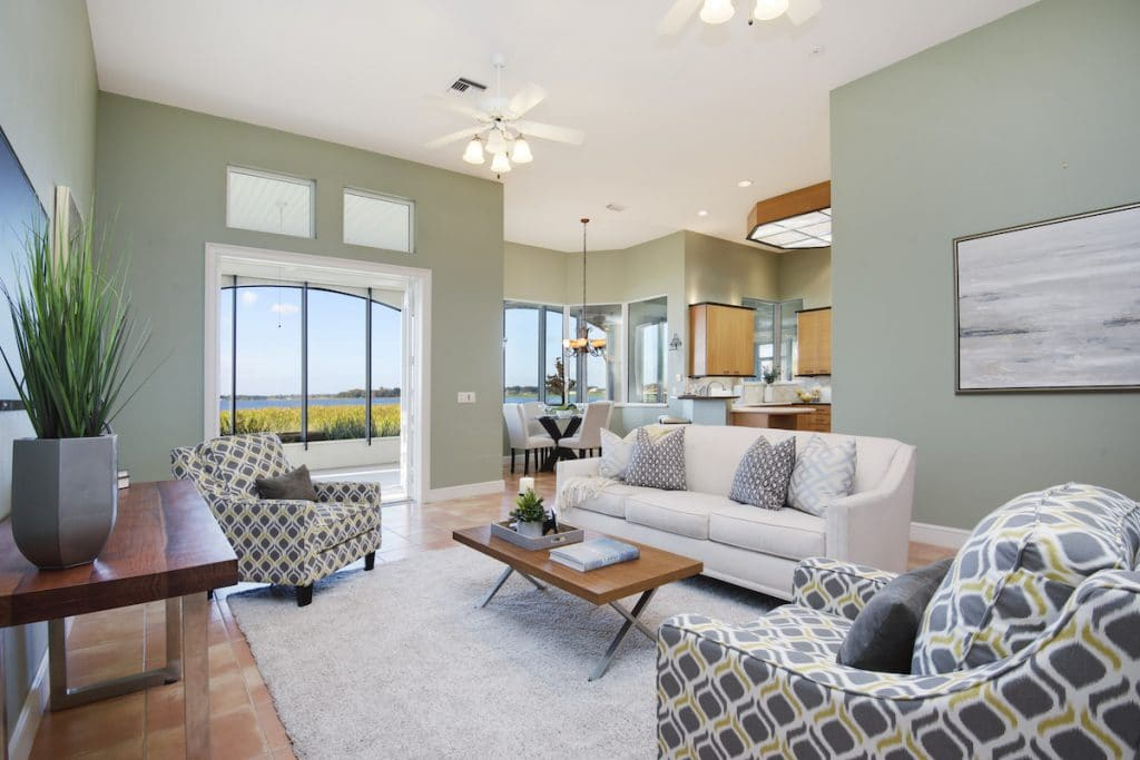 Living room with light green walls, light colored sofa, and patterned accent chairs.