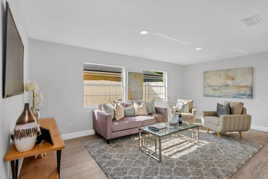 A living room with area carpet, lavendar sofa, artwork, and accent chairs.