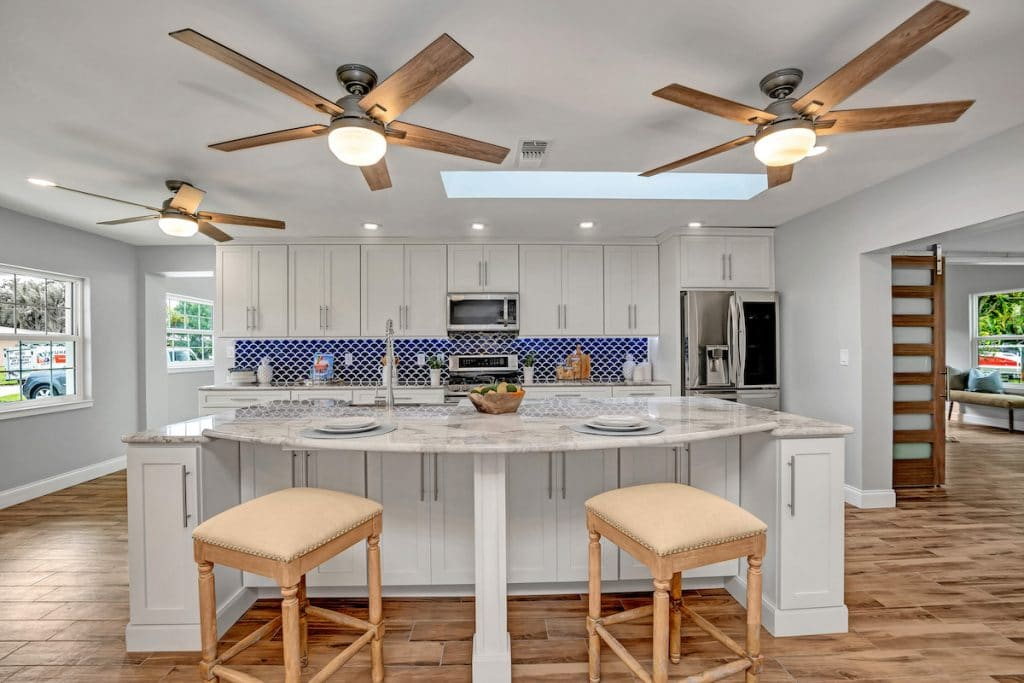A clutter-free kitchen with white cabinetry and three ceiling fans.