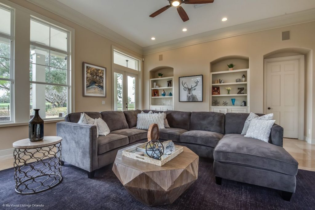 A living room with beige walls and gray sectional.
