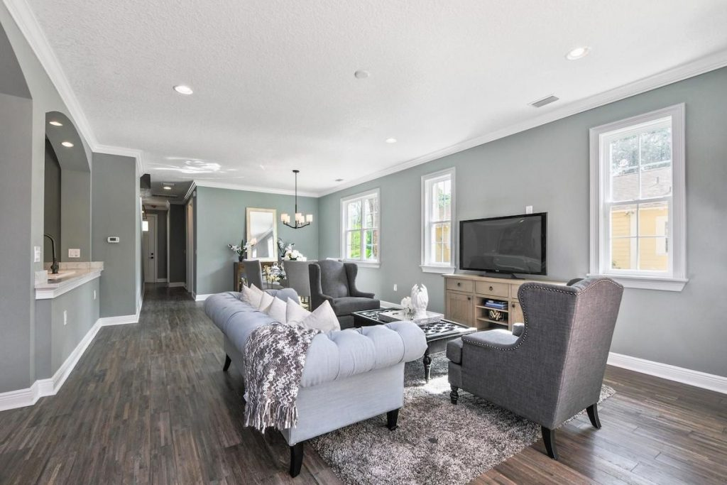 A living room with muted green walls paired with gray and light blue accents.