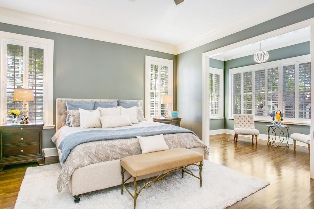 A bedroom with muted green walls, white rug, and night stands.